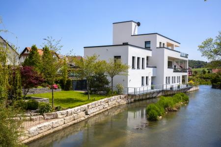 rebau-Referenzprojekte - Wohnungsbau - Einfamilienhaus mit Flachdach, am Bach mit Uferbefestigung