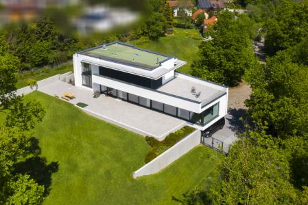 rebau-Referenzprojekte - Wohnungsbau - Einfamilienhaus mit Flachdach und einer Sichtbetonwand als Hangsicherung